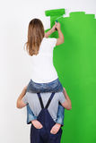 Improvising when you do not have a ladder. As a young women sits on her husbands shoulders to gain extra height Stock Image