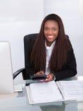 Impuesto calculador de la empresaria confiada en el escritorio Imágenes de archivo libres de regalías