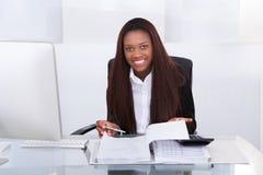 Impuesto calculador de la empresaria confiada en el escritorio Imagen de archivo