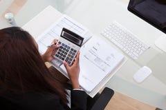 Impuesto calculador de la empresaria confiada en el escritorio Fotografía de archivo
