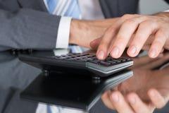 Impuesto calculador del contable usando la calculadora Imágenes de archivo libres de regalías