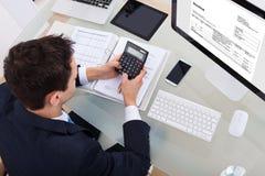 Impuesto calculador del hombre de negocios Imágenes de archivo libres de regalías