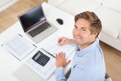 Impuesto calculador del hombre de negocios en el escritorio Fotografía de archivo