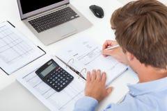 Impuesto calculador del hombre de negocios en el escritorio Fotos de archivo libres de regalías