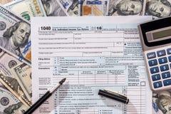 impuesto 1040 con de dólar billete de banco, pluma Imagen de archivo libre de regalías