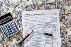 impuesto 1040 con de dólar billete de banco, pluma y calculadora Fotos de archivo