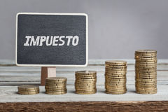 Impuesto, Spanish text for Tax on board, growing stacks of money Stock Photography
