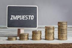 Impuesto, texto español para el impuesto a bordo, creciendo pilas de dinero Fotografía de archivo