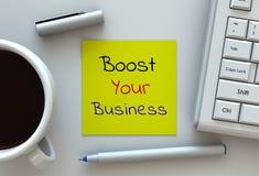 Impulse su negocio, el mensaje en el papel de nota, el ordenador y el café imagen de archivo