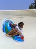 Impulsión alegre negra de la muchacha con el tubo en la diapositiva que transporta en balsa Fotos de archivo libres de regalías
