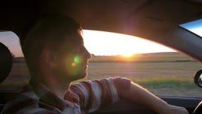 Impulsión caucásica del hombre en el coche en el fondo de la puesta del sol almacen de metraje de vídeo