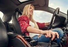 Impulsión de la mujer joven un coche Fotos de archivo libres de regalías