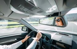 Impulsión de la mujer que un coche refleja en espejo trasero de la visión imagenes de archivo