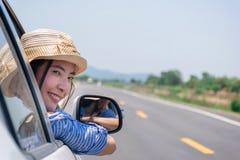 Impulsión de la mujer un coche en el camino con la montaña Imágenes de archivo libres de regalías