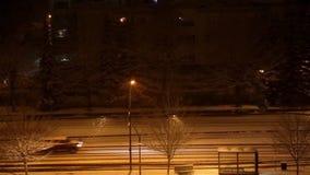 Impulsión de los coches en la noche en tormenta de la nieve almacen de metraje de vídeo