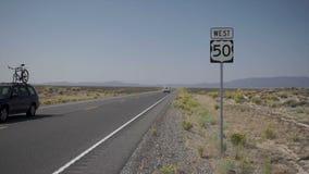 Impulsión de los vehículos a lo largo de un camino en el desierto metrajes