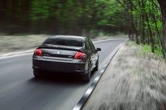 Impulsión de Peugeot 407 del coche en el camino forestal del campo del asfalto en el d3ia Fotografía de archivo