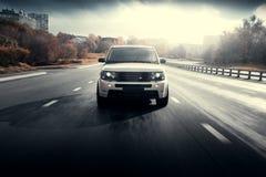 Impulsión de Rover Range Rover de la tierra de los coches en el camino de ciudad del asfalto en el d3ia soleado del otoño Foto de archivo