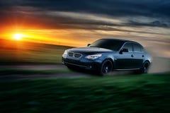 Impulsión del coche en el camino del campo en la puesta del sol Fotos de archivo
