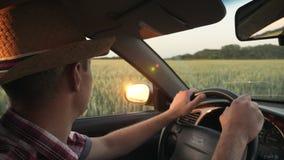 Impulsión del granjero a través del campo en el coche almacen de video