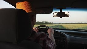 Impulsión del granjero a través del campo en el coche metrajes