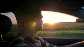 Impulsión del hombre en el coche en el fondo de la puesta del sol almacen de metraje de vídeo