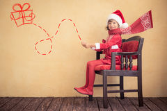 Impulsión del niño en el trineo imaginario de Papá Noel Foto de archivo