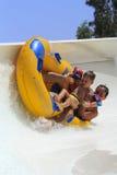 Impulsión del padre y del sol con el tubo en la diapositiva que transporta en balsa Imagenes de archivo