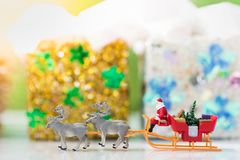 Impulsión miniatura de Santa Claus un carro con un reno durante las nevadas El usar como concepto en día de la Navidad Fotos de archivo