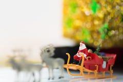 Impulsión miniatura de Santa Claus un carro con un reno durante las nevadas El usar como concepto en día de la Navidad Foto de archivo