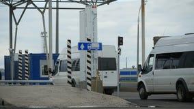 Impulsión moderna blanca de las furgonetas a través del punto de control con las barreras