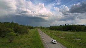 Impulsiones blancas de la cruce a lo largo de la carretera de asfalto dañada almacen de metraje de vídeo