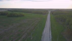 Impulsiones blancas del coche del camino de tierra a la carretera en el crepúsculo almacen de metraje de vídeo