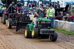 Impulsiones de un hombre joven en un tirón del tractor del césped imagen de archivo