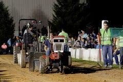 Impulsiones de un hombre joven en un tirón del tractor del césped imágenes de archivo libres de regalías