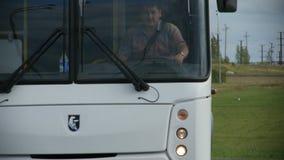 Impulsiones del autobús del primer a lo largo de la carretera contra césped verde
