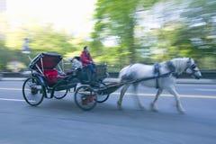 Impulsiones del caballo y de carro en del tráfico el Central Park abajo del oeste en Manhattan, New York City, NY Fotografía de archivo libre de regalías