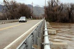 Impulsiones del coche sobre el puente durante la inundación Foto de archivo libre de regalías