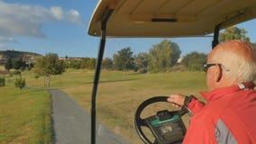 Impulsiones del hombre en el coche del golf almacen de metraje de vídeo