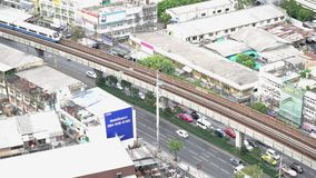 Impulsiones del tráfico a través de las calles de Sukumwit Coches, tren de cielo y gente caminando en el camino de Sumkumwit en l almacen de metraje de vídeo