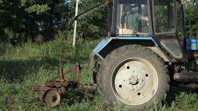 Impulsiones del tractor sobre el campo de la patata Cosechando las patatas con usar el tractor almacen de video