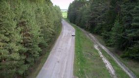 Impulsiones modernas blancas de la cruce a lo largo de la opinión superior de la carretera de asfalto almacen de metraje de vídeo