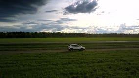 Impulsiones modernas del automóvil a lo largo de la opinión aérea del camino de tierra almacen de metraje de vídeo