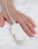 Impulsoximeter auf der Hand des Patienten. Medizinischer Hintergrund. Lizenzfreies Stockbild