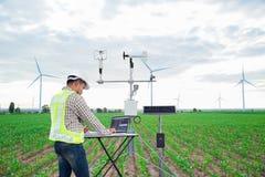 Inżynier używa pastylka komputer zbiera dane z meteorologicznym instrumentem mierzyć wiatrową prędkość, temperaturę i wilgotność, obrazy royalty free