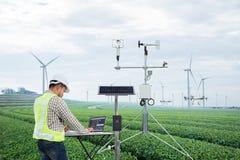 Inżynier używa pastylka komputer zbiera dane z meteorologicznym instrumentem mierzyć wiatrową prędkość, temperaturę i wilgotność, zdjęcia stock