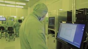 Inżyniera naukowiec w bezpłodnych kostiumach, maska jest w czystej strefie patrzeje proces technologicznie posuwającą się naprzód zbiory