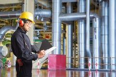 Inżynier bierze notatki dla konserwaci w elektrowni zdjęcie stock