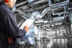 Inżynier bierze notatki przy termiczną elektrowni fabryką zdjęcie royalty free