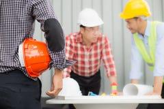 Inżynier i budowy drużyna jest ubranym zbawczego hełm i przyglądającego projekt na stole Fotografia Royalty Free